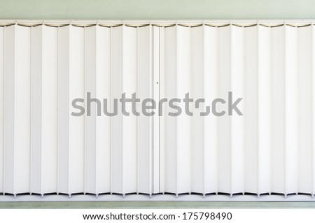 Accordion window blinds of concession stand before opening of baseball season in public park - stock photo
