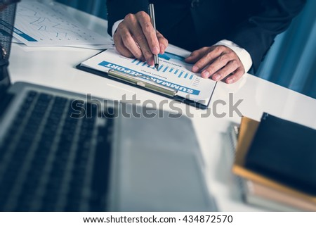 Accountant business man working serious financial reporting and analysis the business profit margin chart statistic in the workplace office. - stock photo