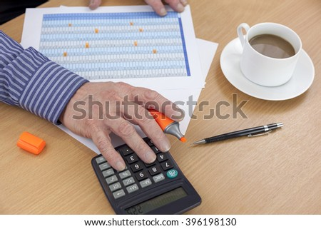 Accountant busy at his desk using a calculator to check a spreadsheet - stock photo