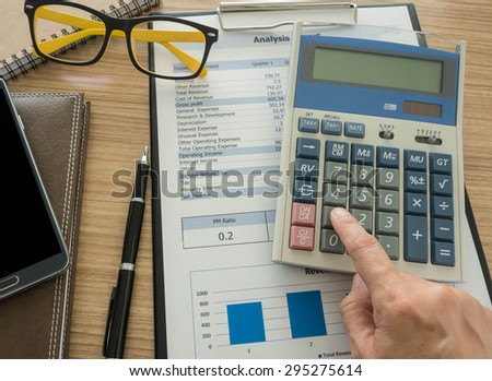 Accountant calculating numbers using a calculator. - stock photo