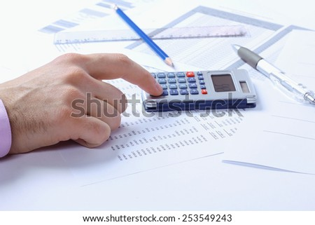 Accountant. Man's hand and calculator. Finance department, accounts, accounting documents. Pens, pencils, papers, ruler and calculator. The man with the calculator. Office worker. Toned image.