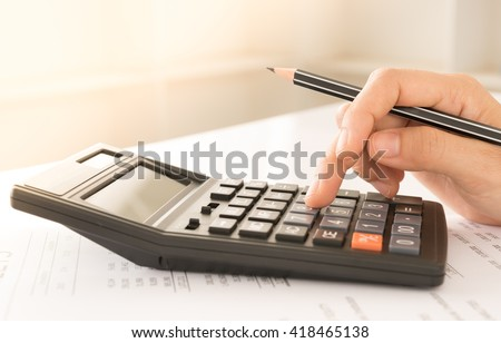 Accountant or Banker using a calculator to calculate the numbers. Concept of Savings, Finances and Accounting. - stock photo