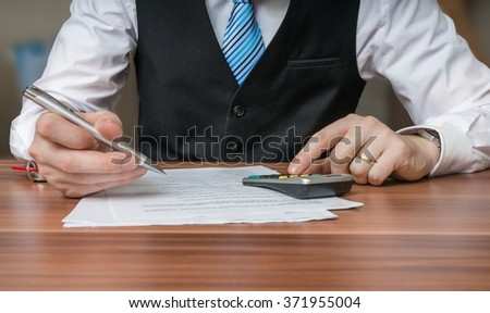 Accountant or business man is calculating taxes with calculator.