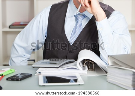 Accountant stares at his calculator wishing for a solution - stock photo