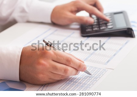 Accountant writing on a business document - stock photo