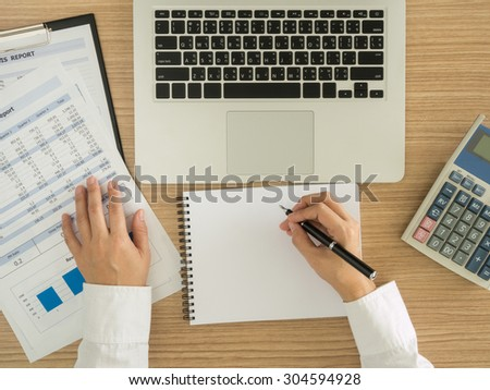 Accountants are analyzing data from the financial statements of the Company. above view. - stock photo