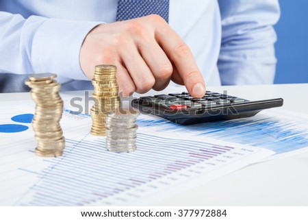 Accountants calculating profit - closeup shot of hands counting coins - stock photo