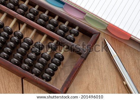 Accounting abacus on wooden table with paper and pen - stock photo