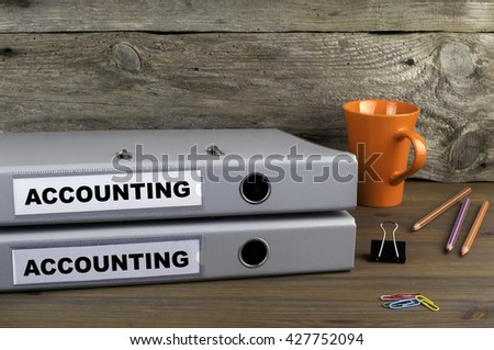 Accounting and Accounting - two folders on wooden office desk - stock photo
