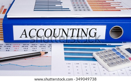 Accounting - blue binder with text on desk in the office - stock photo