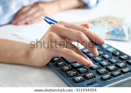 Accounting concept.Analyzing finance report with calculator - stock photo