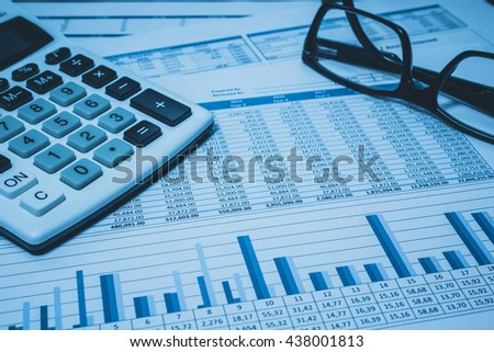 Accounting financial banking stock spreadsheet  with accountant  data with glasses and calculator in blue