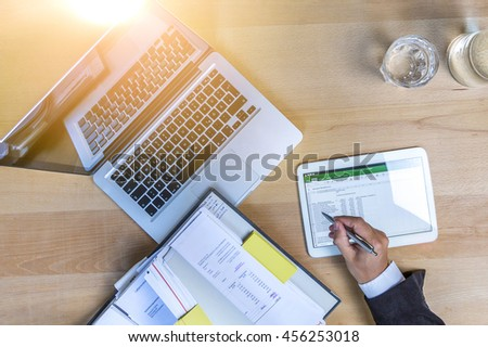 Accounting on a tablet computer and laptop, close-up - stock photo