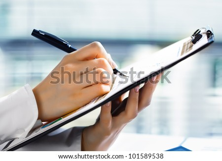 Accounting. Woman's hand with a pen writing on the business paper - stock photo