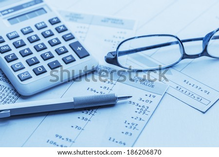 accounting work space with calculator,pen, glasses and profit and loss statements - stock photo