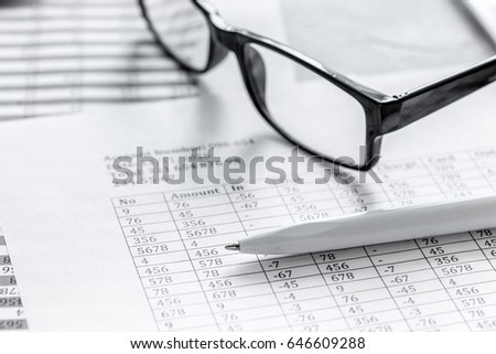 accounting work space with glasses, profit and tables on stone desk close up
