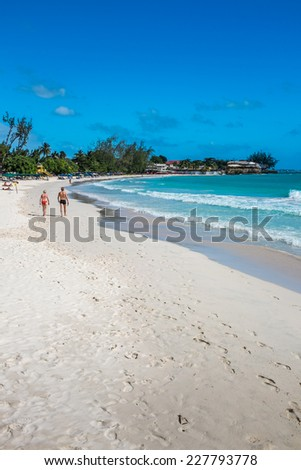 ACCRA BEACH, BARBADOS - DECEMBER 12, 2013 : Sun loungers and shades lining Accra Beach on the south coast of the Caribbean island of Barbados in the West Indies. Accra is also known as Rockley Beach.