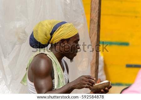 ACCRA, GHANA - Jan 8, 2017: Unidentified Ghanaian man in headscarf puts his fingers into the mouth at the local market. People of Ghana suffer of poverty due to the economic situation
