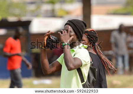 ACCRA, GHANA - Jan 8, 2017: Unidentified Ghanaian young man in a hat and with bag raises his hands. People of Ghana suffer of poverty due to the economic situation