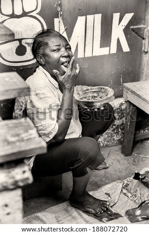 ACCRA, GHANA - MAR 4, 2012: Unidentified Ghanaian woman eats  in the street. People of Ghana suffer of poverty due to the difficult economic situation