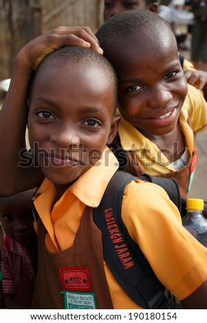ACCRA, GHANA - MARCH 18: Unidentified African student kids  greeting to tourists after school  on March 18, 2014 near Nima, Accra, Ghana. Nima is one of the most deprived community in Ghana.