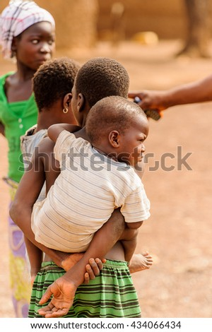 ACCRA, GHANA - MARCH 6, 2012: Unidentified Ghanaian boy carries his little brother on his back in the street in Ghana. Children of Ghana suffer of poverty due to the unstable economic situation