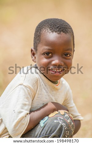ACCRA, GHANA - MARCH 6, 2012: Unidentified Ghanaian boy smiles and poses in the street in Ghana. Children of Ghana suffer of poverty due to the unstable economic situation