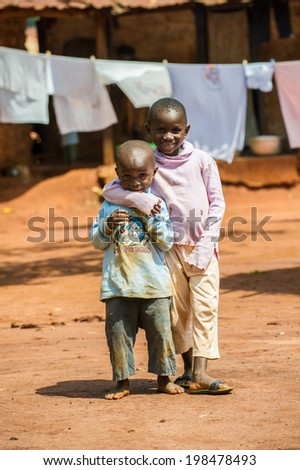 ACCRA, GHANA - MARCH 5, 2012: Unidentified Ghanaian girl hugs her brother in the street in Ghana. Children of Ghana suffer of poverty due to the unstable economic situation