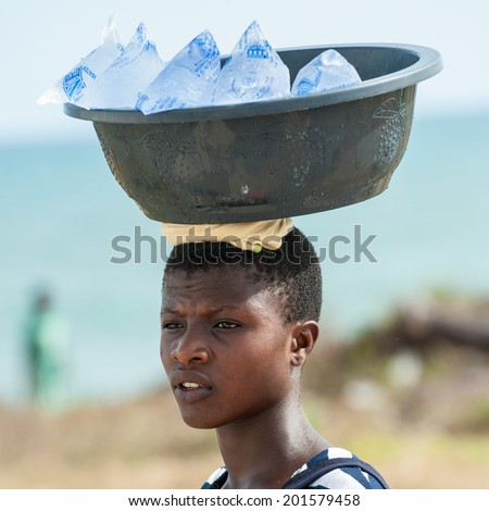 ACCRA, GHANA - MARCH 2, 2012: Unidentified Ghanaian girl sells cold water bags on her head. People of Ghana suffer of poverty due to the unstable economic situation - stock photo