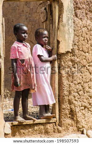 ACCRA, GHANA - MARCH 6, 2012: Unidentified Ghanaian girl stays near the house in the street in Ghana. Children of Ghana suffer of poverty due to the unstable economic situation