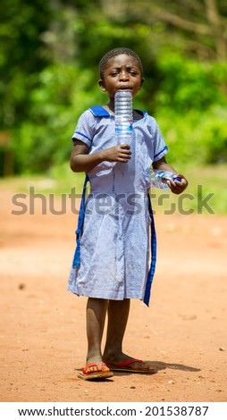 ACCRA, GHANA - MARCH 5, 2012: Unidentified Ghanaian girl with an empty bottle in the street in Ghana. Children of Ghana suffer of poverty due to the unstable economic situation