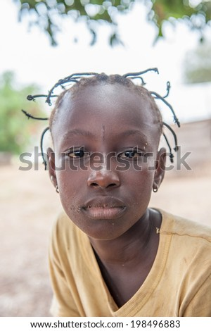 ACCRA, GHANA - MARCH 6, 2012: Unidentified Ghanaian girl with pigtails in the street in Ghana. Children of Ghana suffer of poverty due to the unstable economic situation