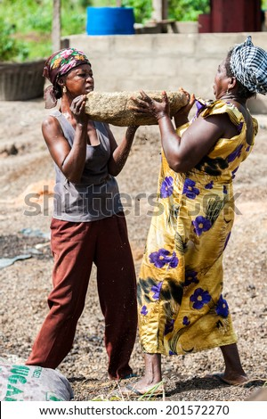 ACCRA, GHANA - MARCH 3, 2012: Unidentified Ghanaian two women transport a stone in Ghana. People of Ghana suffer of poverty due to the unstable economic situation - stock photo