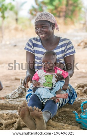 ACCRA, GHANA - MARCH 6, 2012: Unidentified Ghanaian woman and her little baby sit near the tree in the street in Ghana. People of Ghana suffer of poverty due to the unstable economic situation