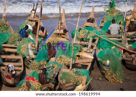 ACCRA, GHANA - MARCH 20: Unidentified group of African fishermen working on Cape Coast beach on March 20, 2014 in Accra, Ghana. Cape Coast is famous fishery village in Ghana. - stock photo