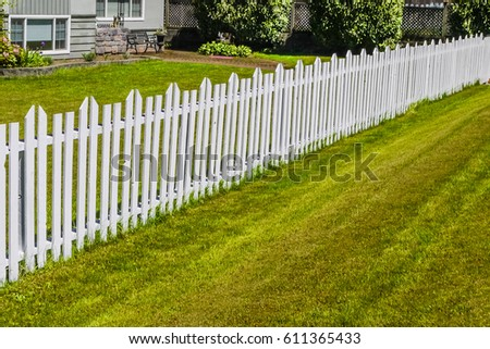 Accurate white wooden fence along the front yard of residential house