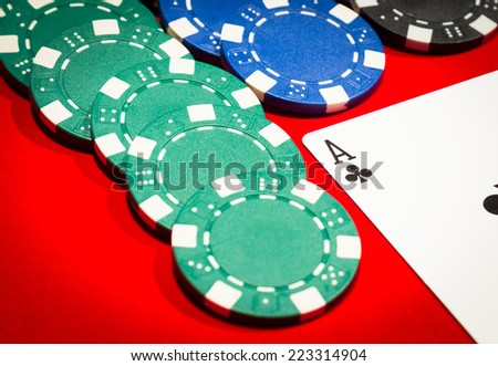 Ace of clubs and chips on a red table - stock photo