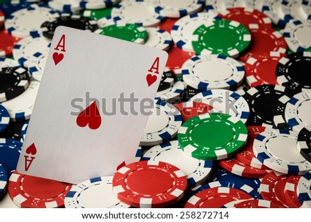 Ace of hearts on many poker chips spread on table