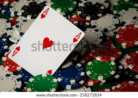 Ace of hearts on many poker chips spread on table - stock photo