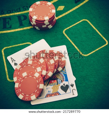 Ace of spades and black jack with red poker chips in the background. - stock photo