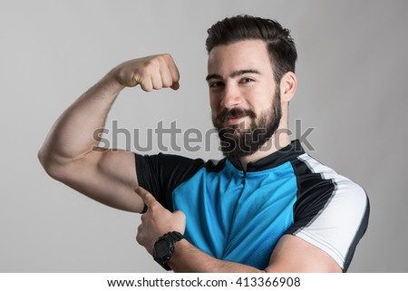 Achievement concept. Portrait of young cyclist flexing his bicep muscle smiling at camera over gray studio background