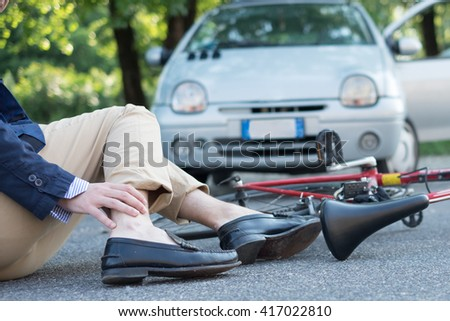 aching man after bicycle accident on the asphalt - stock photo