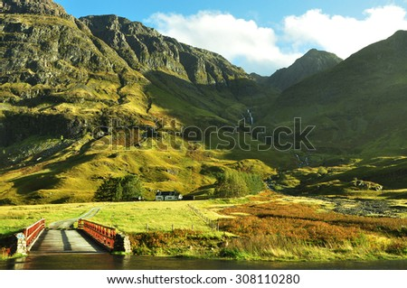 Achnambeithach cottage and a bridge at the mountain edge in Glencoe, Scottish Highlands  - stock photo