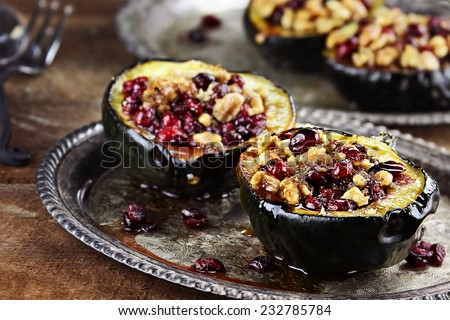 Acorn squash stuffed and baked with butter, brown sugar, walnuts and cranberries, ready for holiday dinners. Extreme shallow depth of field with beautiful bokeh. - stock photo