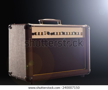 acoustic guitar amplifier on the dark background with back light right - stock photo