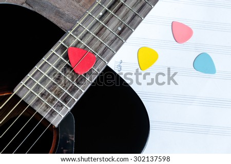 acoustic guitar and colorful picks on blank music sheet for music background - stock photo
