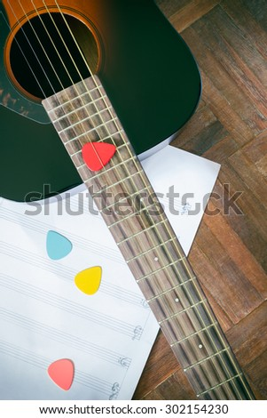 acoustic guitar and colorful picks on music sheet for music background - stock photo
