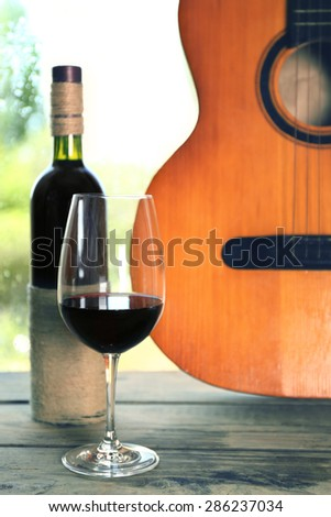 Acoustic guitar and glass of wine next the window with rain drops - stock photo