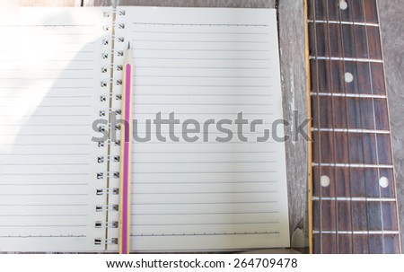 Acoustic guitar and notebook - stock photo