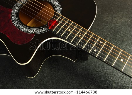 Acoustic guitar and plectrum on black